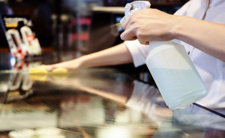 homem limpando mesa de vidro